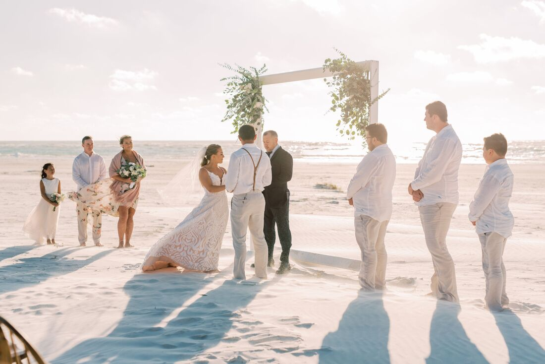 Bride and groom exchanging wedding vows on Siesta Key surrounded by family and friends