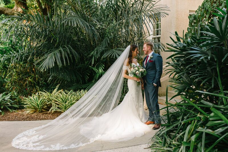 Jennifer Matteo Event Planning – Sarasota wedding planner – Sarasota luxury wedding planner – Sarasota weddings- Sarasota luxury weddings – Marie Selby Botanical Gardens – Marie Selby Gardens – Marie Selby Gardens wedding - bride with long veil - groom in blue suit