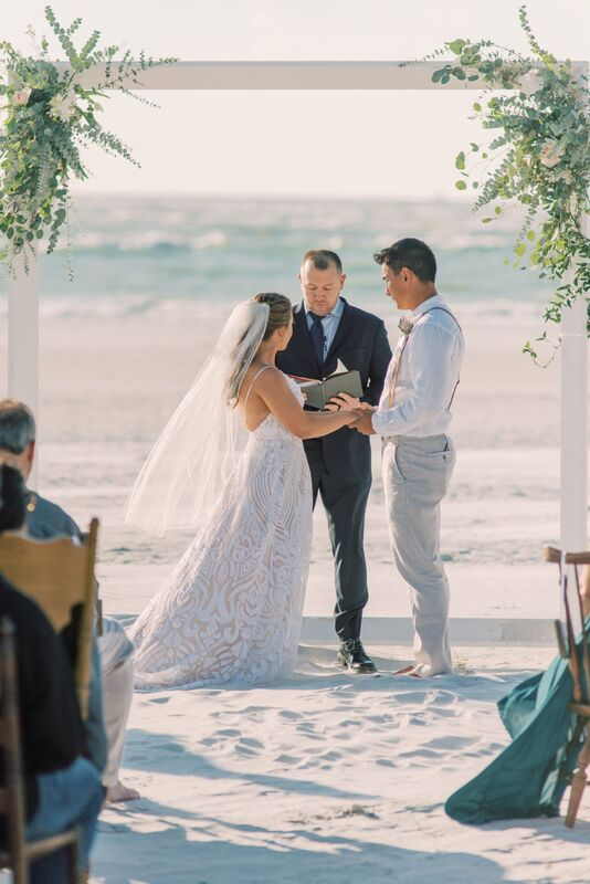 Bride and groom exchanging wedding vows on the beach at the Sunset Beach Resort on Siesta Key