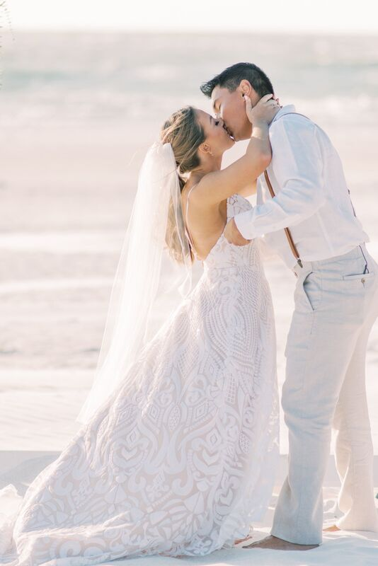 Just married! Newlywed couple kissing during their Sunset Beach Resort beach wedding