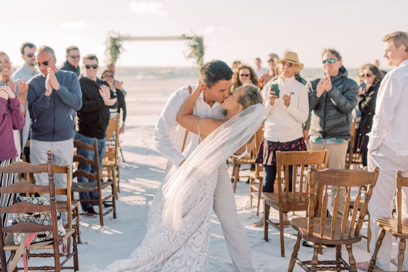 Wedding guests cheering as couple kiss after their Sunset Beach wedding