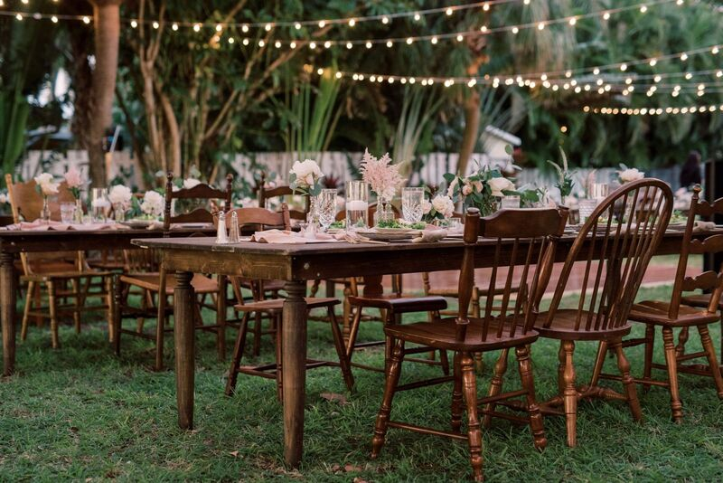 Outdoor wedding reception set with rustic wooden farmhouse tables and mismatched wooden dining chairs