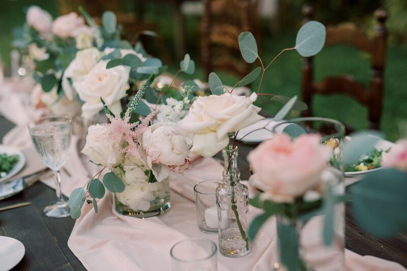 Pink table runner dotted with eclectic glassscontainers and pink and white flowers