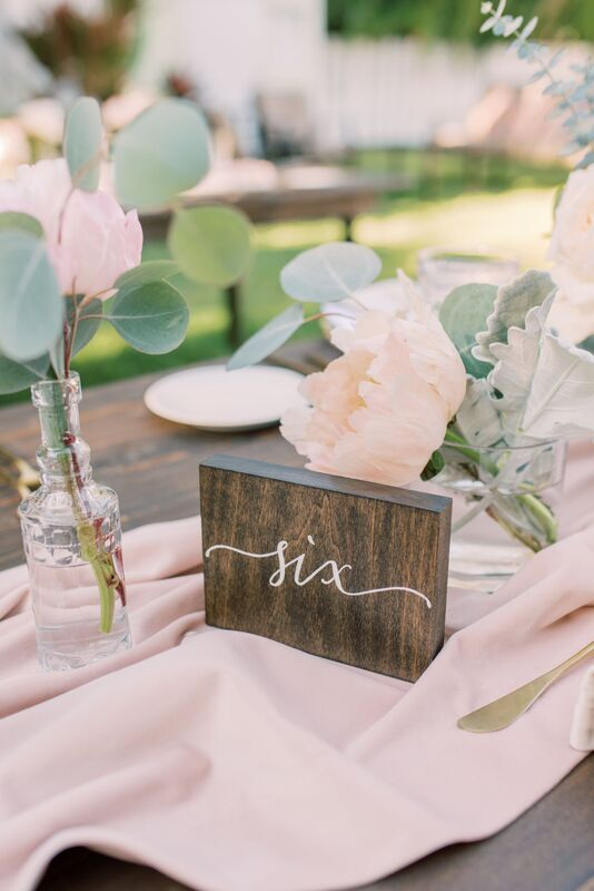 Rustic wooden table numbers paired with soft romantic pink florals and vintage glassware for an outdoor Siesta Key wedding