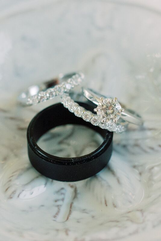 Black grooms wedding band with delicate diamond wedding bands for his bride