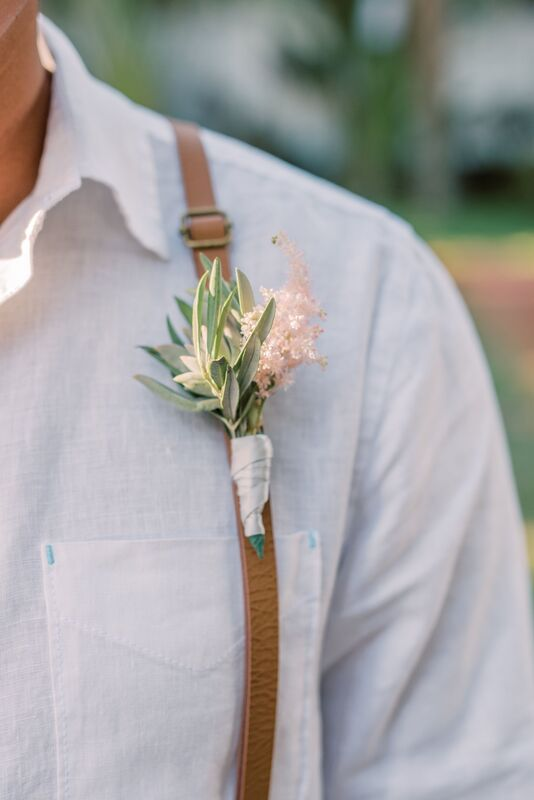 delicate wedding boutonniere of greenery and pink astilbe pinned to the grooms leather suspenders